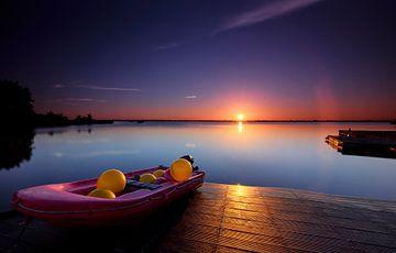 Ein kleines rotes Boot voll von farbigen Bojen von