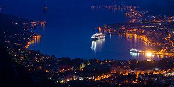 Kreuzfahrtschiff weit unten in der Bucht zwischen den Bergen in der Nähe der Stadt, tropische Nacht. von Michael Semenov