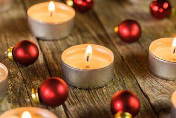 Brandende adventskaars vlammen met rode kerstballen ornamenten van Alex Winter