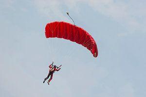 Parachutist aan een rode parachute tegen een blauwe lucht