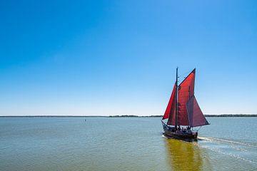 Fishing boat on a lake with blue sky van Rico Ködder