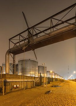 Scène de nuit avec des silos, viaduc et route pavée sur Tony Vingerhoets
