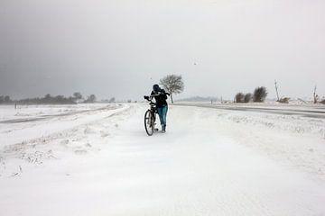 Meisje met fiets in sneeuwstorm in Zeeland von Wout Kok