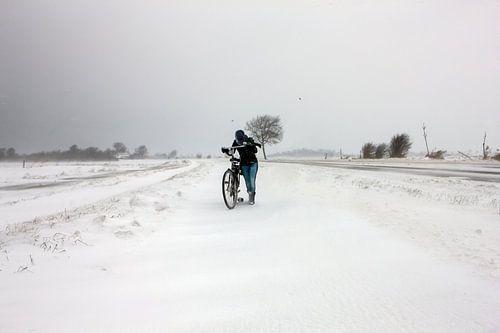 Meisje met fiets in sneeuwstorm in Zeeland van