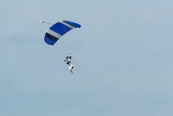 Parachutist aan een blauwe parachute tegen een licht blauwe achtergrond