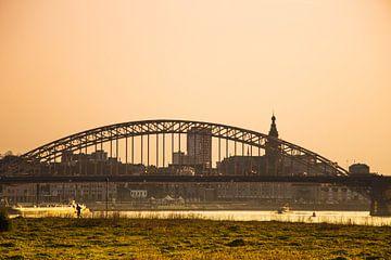 Waalbrug bij zonsondergang met de stad Nijmegen op de achtergrond. van Rianne Groenveld