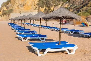 Reihen mit Strandschirmen und blauen Sonnenbetten auf Strand in Albufeira Portugal von