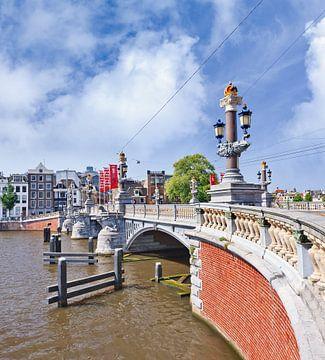 Oude brug tegen een blauwe bewolkte hemel in Amsterdam van Tony Vingerhoets
