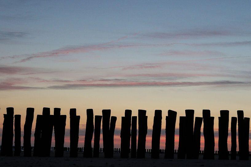 golfbrekers met ondergaande zon op het strand in zeeland van Frans Versteden