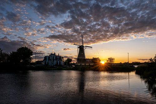 Zonsondergang met Nederlandse windmolen in de wateren van Kralingse Plas, Rotterdam, Nederland