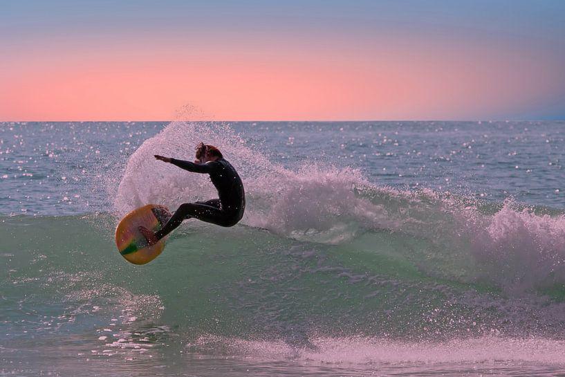 Surfer surft op een golf op de caribbische zee bij Aruba van Nisangha Masselink