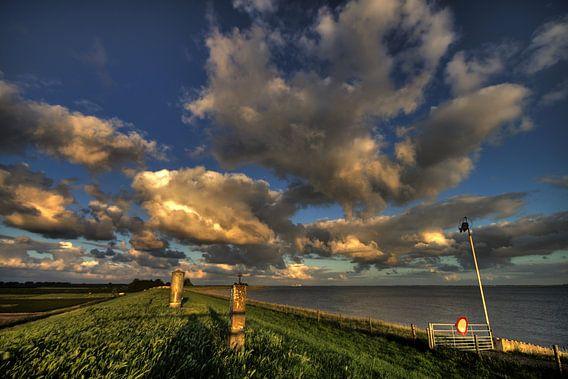 Wolkenlucht met strijklicht bij het water