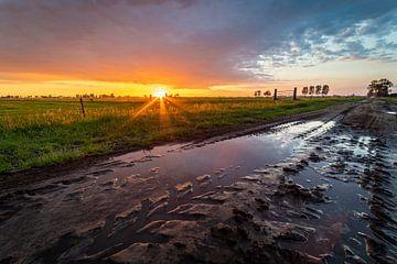 zonsondergang boven een natte zandweg van Yorben  de Lange
