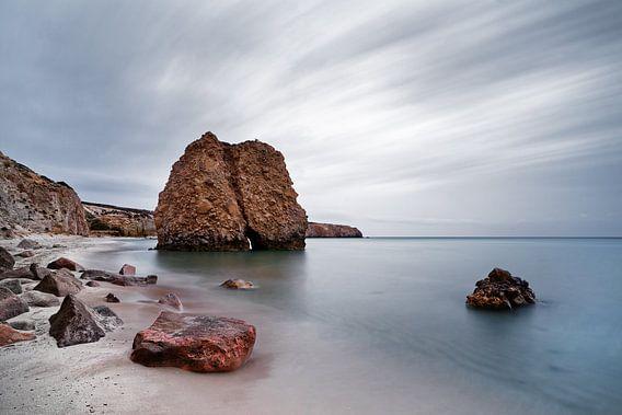 Strand met roodachtige steenblokken, water en wolkenbeweging
