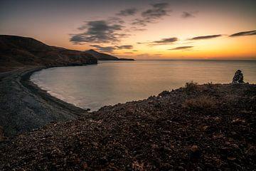 Fuerteventura, zonsopgang op een stenen strand met uitzicht over de baai naar de zee van Fotos by Jan Wehnert