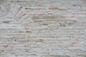 Eine helle Wand aus Ziegelsteinen mit einem Rundbogen von Ulrike Leone