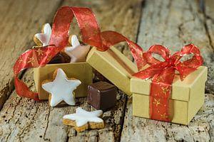 Biscuits de Noël en forme d'étoile et cadeau en chocolat avec ruban rouge sur une table en bois sur Alex Winter