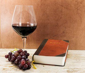 glas rode wijn op een tafel met een bijbel