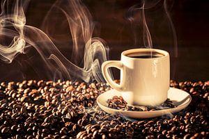 11507469 Kopje dampende koffie op een bed van koffiebonen