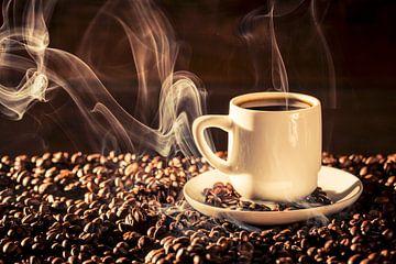 11507469 Tasse de café fumant sur un lit de grains de café sur BeeldigBeeld Food & Lifestyle