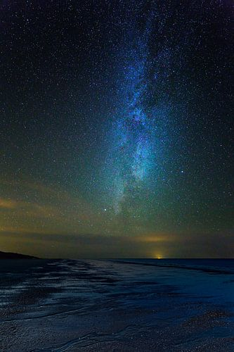 Melkweg boven een Nederlands strand van