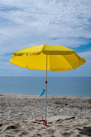 Parasol op strand met mondkapje