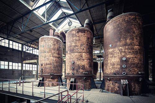 Roestige kook- of verdamppannen in een verlaten suikerfabriek.