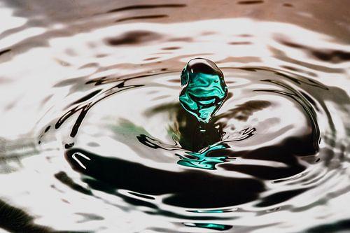 Groene waterdruppel valt of wateroppervlak