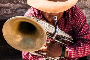 Een muzikant speelt een deuntje op zijn blaasinstrument