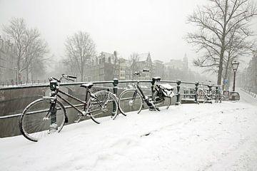 Radfahren auf dem Kanal im verschneiten Amsterdam von Nisangha Masselink