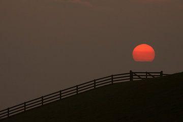 Zonsondergang aan de Waddenzeedijk van de Friese Waddenkust van