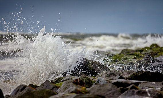 Ruige zee met opspattend water op de golfbrekers van Texel van Martijn van Dellen
