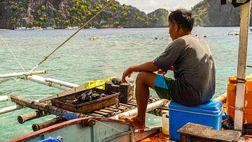Visser bereidt vis op boot (Filipijnen) van Jessica Lokker