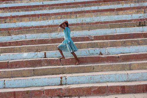Meisje loopt op een gekleurde trap aan de oever van de Ganges in Varanasi India