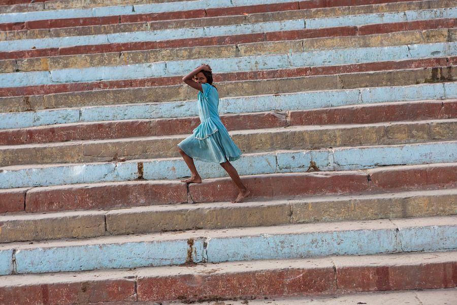 Meisje loopt op een gekleurde trap aan de oever van de Ganges in Varanasi India van Wout Kok