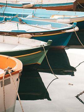 Gekleurde vissersbootjes in de haven van Procida reflecterend in de zee van Michiel Dros