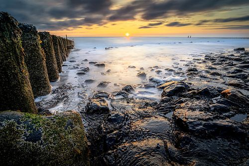 Golfbreker aan de Zeeuwse kust bij zonsondergang