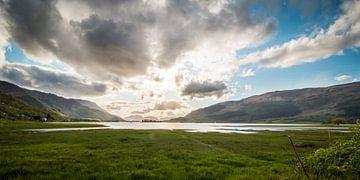 Zon  schijnt achter de wolken in Schotland van Marcel Keurhorst