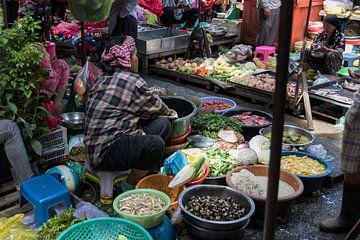 Een marktvrouw in een kraampje op de markt van Phnom Penh van