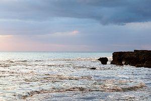 Zonsondergang aan de kust in Jamaica, met turquoise zee en blauw roze lucht.