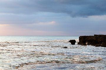 Coucher de soleil sur la côte jamaïcaine, avec une mer turquoise et un ciel bleu rose.