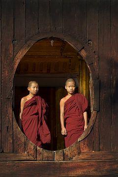 Jonge boedhistische monniken bij een houten raam in Myanmar sur Nisangha Masselink
