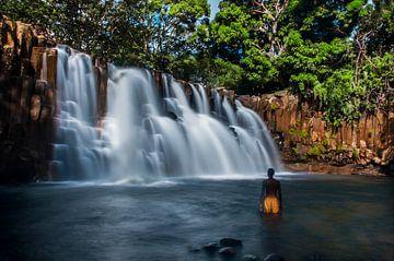 Tropischer Wasserfall mit lokalen in gelben Badehosen von Corrine Ponsen