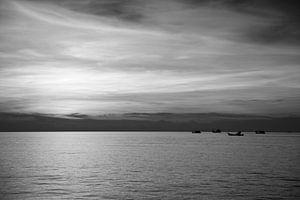 Zeezicht met zonsondergang en bootjes.