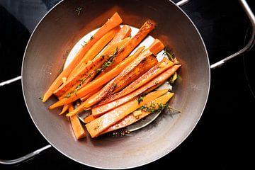 wortelgroenten, geglazuurde wortelen met tijm, gember en honing in een ijzeren pan op het zwarte for van Maren Winter