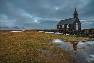 Ein bewölkter Wintertag in der schwarzen Kirche in Budir, mit einer Spiegelung der Kirche im See vor von Anges van der Logt