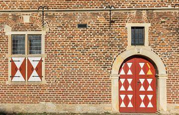 Rode deur in de bakstenen muur van het historische kasteel van Raesfeld van Marc Venema