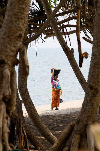 Een Balinese vrouw lopend langs het strand van