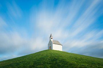 Kirche auf einem Hügel unter bewegten Wolken von iPics Photography