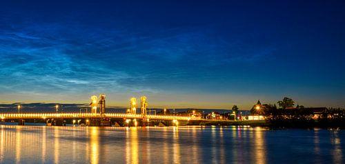 Stadsbrug over de IJssel in Kampen met lichtende nacht wolken